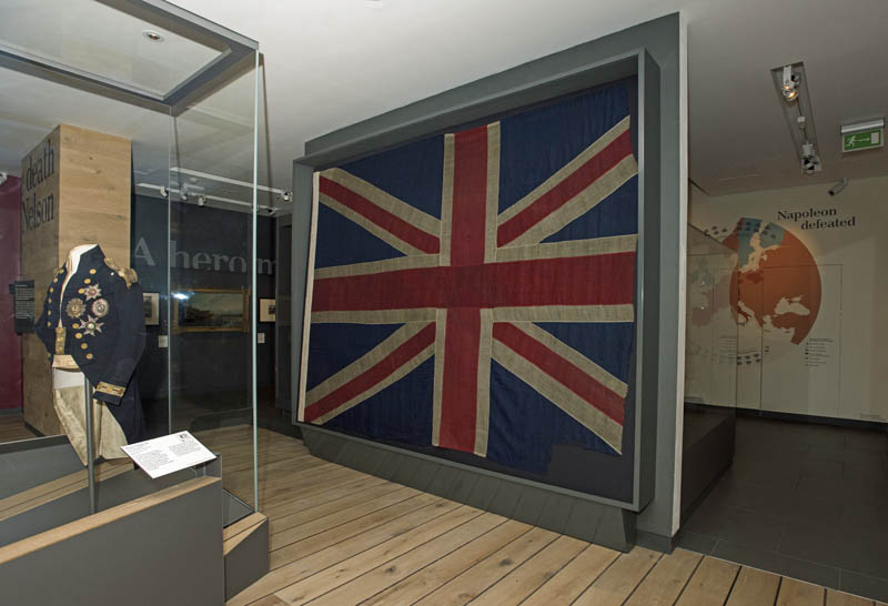 The Selling Flag on display in Nelson, Navy, Nation Gallery with Textiles Consrvator Nicola Yates and her Intern and Curator, Quintin Colville